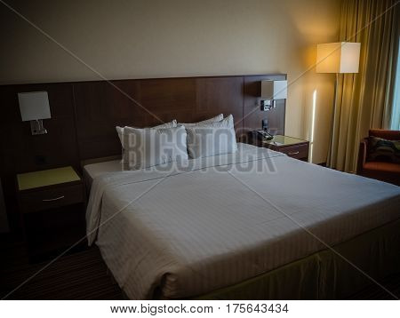King-size bed with bedside table curtain and lamp