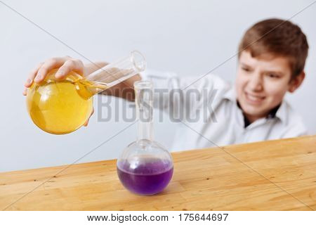 Chemical reaction. Nice pleasant concentrated boy holding a flask and pouring chemical reagent into the other flask while carrying out the experiment
