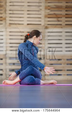 fitness, sport, training and lifestyle concept - smiling woman stretching leg on mat in gym. Blue sportwear. Pink yoga mat. Profile of women. Health lifestyle.