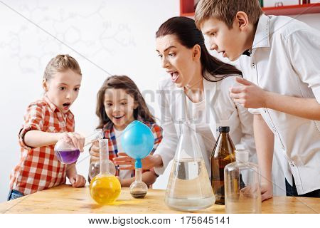 Having fun. Delighted curious positive children standing around the table and mixing chemical reagents while conducting an experiment