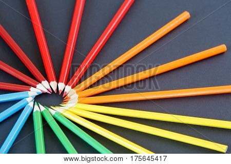 color pencils arranged in a circle top left on dark background, top view. Creative cocept. Drawing and painting. Artist. Schoo and education.