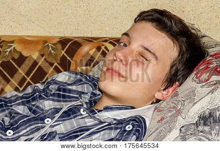 The guy closed one eye lying on the couch