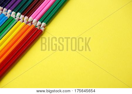 Colored pencils angle. Many different colored pencils on yellow background. Place for text. Drawing and painting. Artist. Art and design.