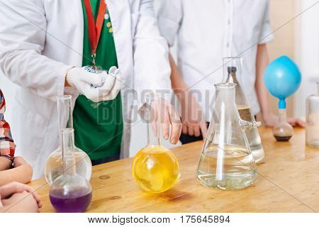 Chemical reaction. Nice experienced intelligent scientist holding a chemical reagent and holding a flask while trying to show an experiment