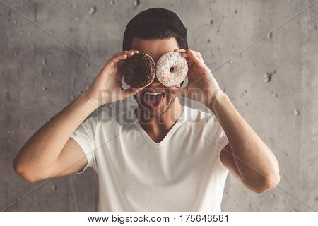 Funny young man in cap is holding doughnuts and showing tongue on concrete wall background