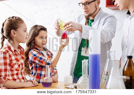 Helping with an experiment. Nice cute delighted girl holding a bottle and looking at the liquid in it while helping with an experiment