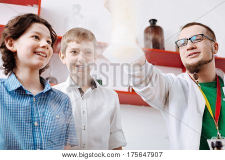 Wonderful science. Nice positive thrilled boys smiling and looking at the chemical smoke while being fascinated by the experiment in the lab
