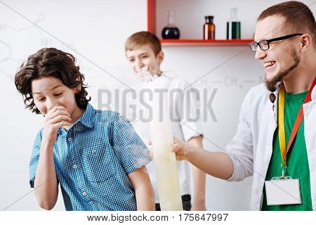 Strong reagents. Joyful curious nice boy covering his mouth and trying not to breathe in the chemical smoke while being in the lab