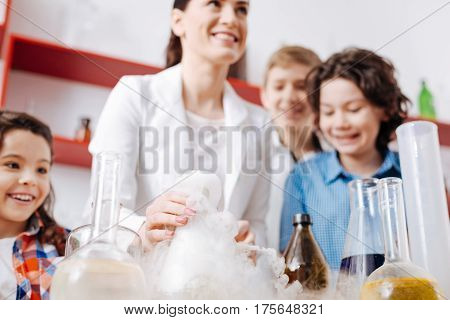 Fuming liquid. Positive cheerful female scientist holding a flask with fuming liquid and laughing while having fun with children