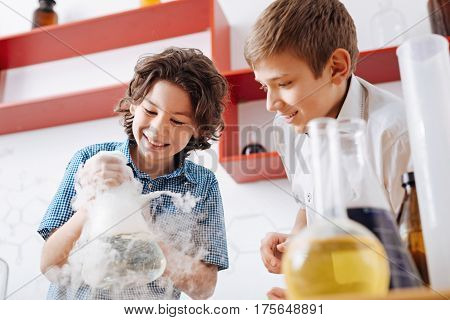 Clever children. Cheerful young future scientists looking at the chemical flask and smiling while being interested in science