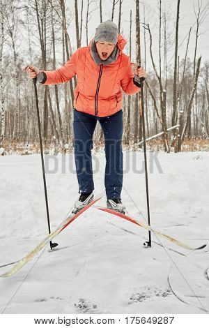 Woman in orange jacket on jumps skis in winter park.