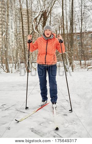 Woman in orange jacket on skis in winter park.