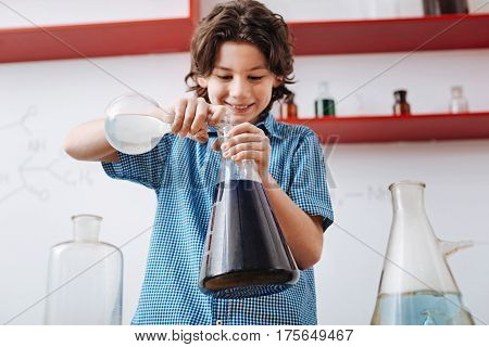 Chemical reaction. Joyful exited smart boy holding flasks and mixing chemical liquids while enjoying his time in the lab