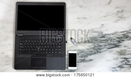 Overhead view of modern wireless mobile cell phone and laptop computer on marble desktop. Paperless office concept.