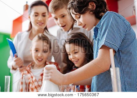 Involved in the process. Smart clever positive child looking at the flask and working with chemical reagents while being supported by his friends