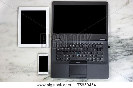 Overhead view of modern wireless mobile communication devices and computer on marble desktop. Paperless office concept.
