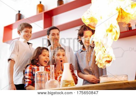 How dangerous. Surprised nice cute children standing in the chemistry lab and looking at the fire while being impressed by the experiment