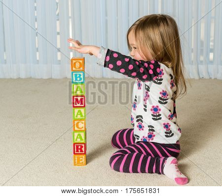 Young female toddler building a tower of wooden blocks at home spelling Obamacare