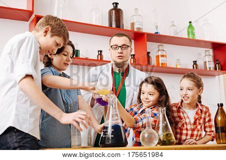 Controlling the experiment. Nice experienced male teacher standing in the classroom and controlling the experiment while having a chemistry lesson