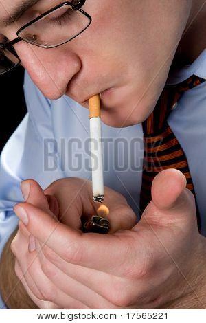 Man lighting a cigarette over black