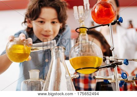 Experimenting with chemicals. Selective focus of a transparent chemical flask with yellow liquid being held by a nice curious boy while experimenting
