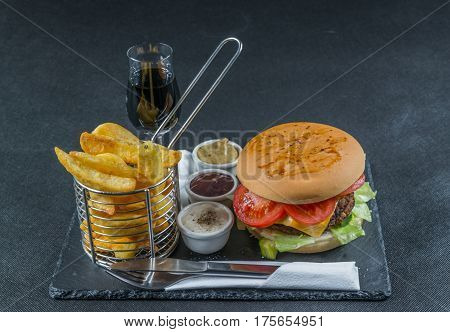 Flame Grilled Double Stack Cheeseburger, Lettuce, Tomato, With Three Sauces, Chips In A Metal Basket