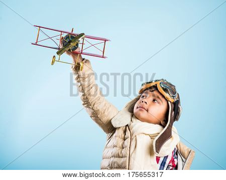 Happy Indian or asian boy kid playing with toy metal airplane against winter sky background - Kid and flying or ambition concept