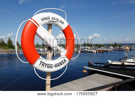 Ranea Sweden - July 23 2016: A red and white lifebuoy at Kangson marina labeled with the insurance company Trygg-Hansa brand.