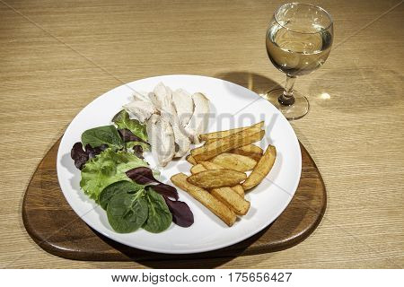 Slimmer's chicken meal with salad fries and wine. Small portion of a healthy meal served with hite wine.