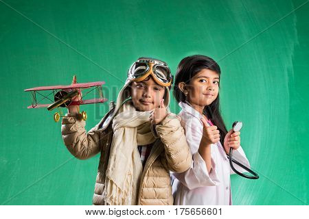 Kids and education concept - Small indian boy and girl posing in front of Green chalk board in pilot fancy dress and doctor costume with stethoscope, wanna pilot or doctor