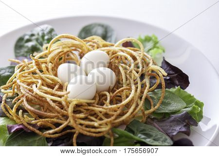 Ethical vegan or vegetarian organic healthy spiralized meal. Boiled quail eggs in fried spiralized potato nest with baby leaf salad.
