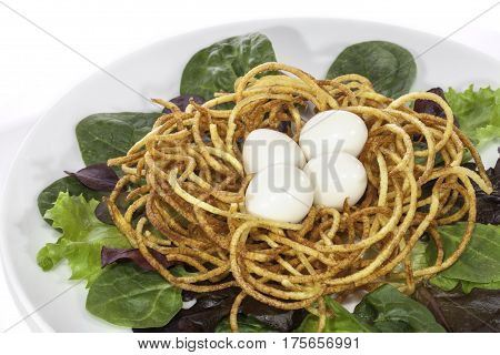 Slimmer's low calorie boiled quail egg salad made with spiralizer. Nest of fried spiralized potato making crispy french fries.