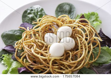 Boiled quail eggs in a spiralized fried potato french fries nest Served with baby leaf salad. Healthy low calorie slimmer's meal made with a spiralizer.