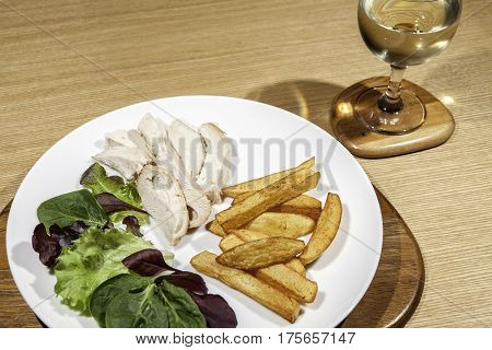 Calorie controlled diet chicken meal with salad and wine. Small portion of white chicken meat with baby lettuce and spinach leaf salad and potato chips. Served with wine.