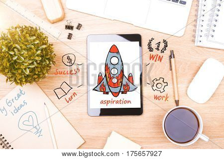 Top view of wooden desktop with rocket ship on smartphone screen. Aspirations concept