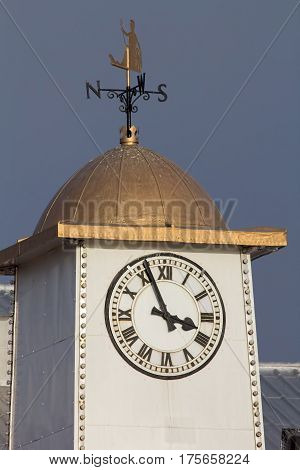 Classic white clock tower with gold Britannia weather vane poster