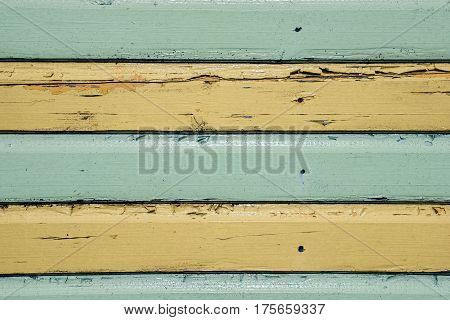 Horizontal green and yellow stripes painted on timber cladding. Flaking paint on wooden planks. Useful colorful background image.