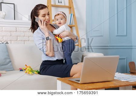 Handling everything. Capable independent modern woman negotiating on new terms for her business while holding her child close to her and working from home
