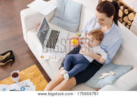 Wanna have some fun. Loving gentle classy mom playing with her child while taking some time off after comparing sales data