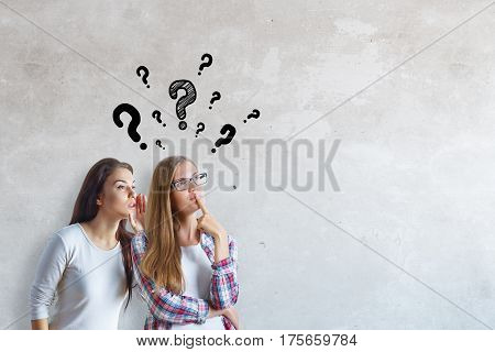 Two attractive thoughtful girls with drawn question marks on concrete wall background. Gossip concept