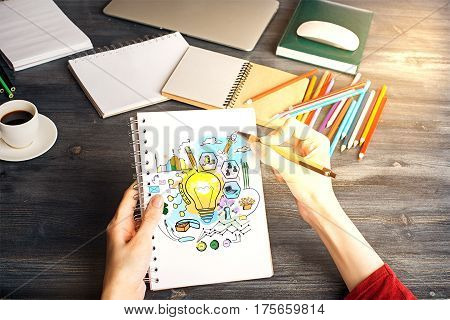 Top view of woman's hands drawing creative sketch in spiral notepad above workplace with coffee cup and supplies. Idea concept