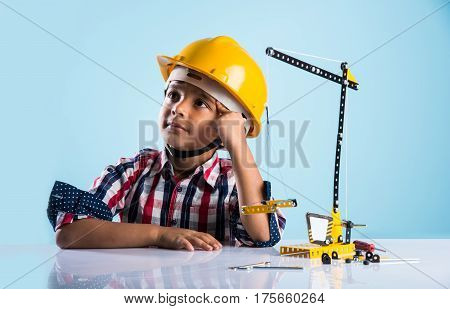 cute indian baby boy playing with toy crane wearing yellow construction hat or hard hat, childhood and education concept