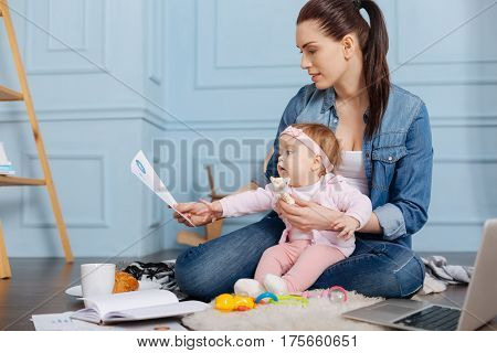 Mastering my proficiency. Competent professional young lady holding up a print of a diagram while her little helper stretching her hand touching it