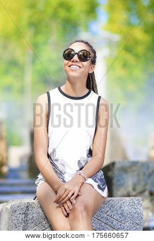 Portrait of Smiling Young African American Teenager Girl With Plenty of Dreadlocks Posing in Park Outdoors.Vertical Image Orientation