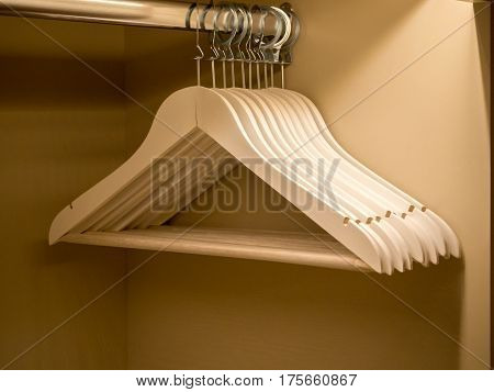 white wooden clothes hanger in the closet