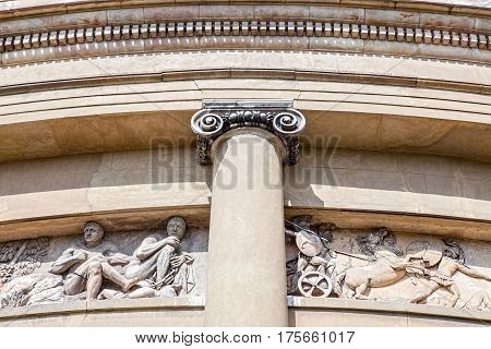 Ancient classical architecture. Ionic column in front of a stone relief mural depicting a centurion chariot battle.
