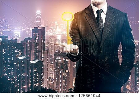 Businessman holding ornate golden key on night city background. Accessibility concept. Double exposure