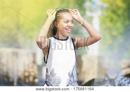 Natural Portrait of Happy Positive African American Teenager Girl With Long Dreadlocks in Sunglasses. In Front of Fountain Outdoors. Horizontal image