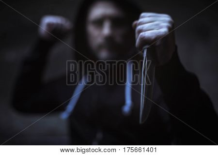 Taking your money away. Antagonized brutal wicked man pointing a dagger at his victim while wearing black hoodie and clenching his fists