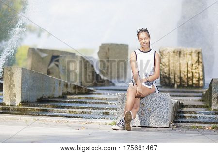 Natural Portrait of Happy Smiling African American Teenager Girl Sitting in Front of Water Fountain Outside. Horizontal Image Orientation
